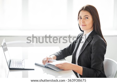 Portrait of young pretty business woman with laptop in the office - stock photo
