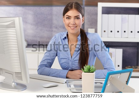 Portrait of young pretty businesswoman sitting at office desk, smiling. - stock photo