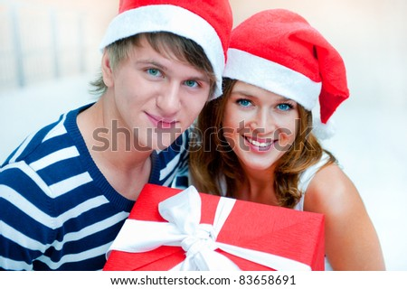 Portrait of young pretty couple standing indoors wearing Santa Claus helper hats and hugging. Holding big red box - christmas gift and looking at camera. Photo from above. Lots of copyspace