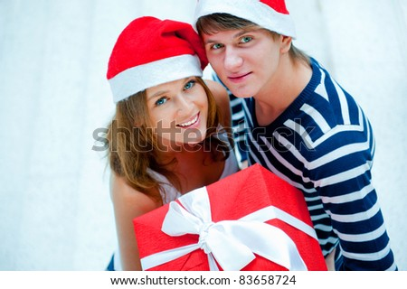 Portrait of young pretty couple standing indoors wearing Santa Claus helper hats and hugging. Holding big red box - christmas gift and looking at camera. Photo from above. Lots of copyspace - stock photo