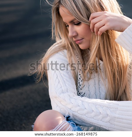 Portrait of young pretty fashionable blonde woman dressed in ripped jeans and white sweater.Close up. - stock photo