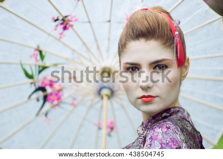 Portrait of young pretty geisha and wearing traditional japanese kimono and traditional umbrella - stock photo
