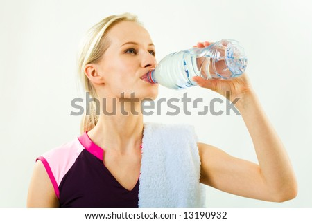 Portrait of young pretty girl drinking water from bottle with towel on her shoulder - stock photo
