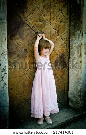 Portrait of young pretty girl in long pink dress standing in front of the old door - stock photo