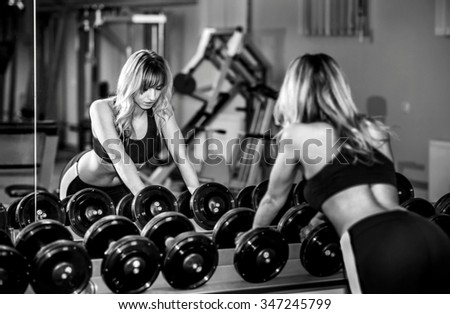 Portrait of young pretty girl training in the gym - stock photo