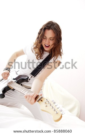 Portrait of young pretty girl who is feeling free and playing guitar in a room - stock photo
