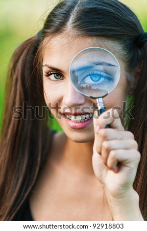 portrait of young, pretty, long-haired girl holding magnifying glass near the eye