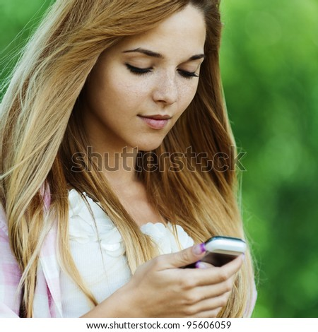 Portrait of young pretty, long-haired, sad woman standing against background of summer green of park, holding mobile phone - stock photo