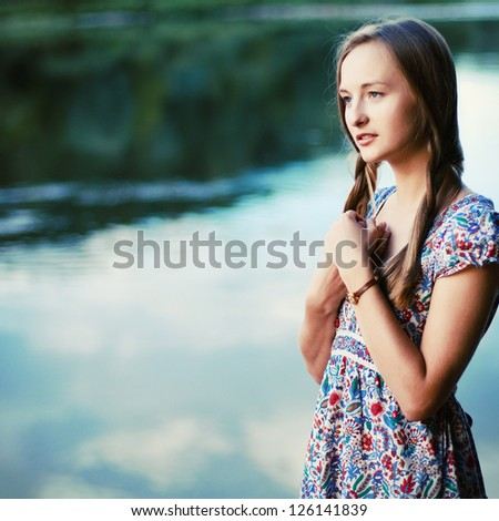 Portrait of young pretty sensual woman. Girl waiting near the river. - stock photo