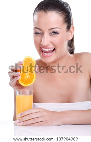 Portrait of young pretty smiling woman holding orange and squeezes the juice from the orange into a glass. Natural fresh juice concept - stock photo
