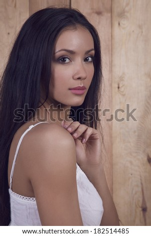 Portrait of young pretty tan woman touching her shoulder.