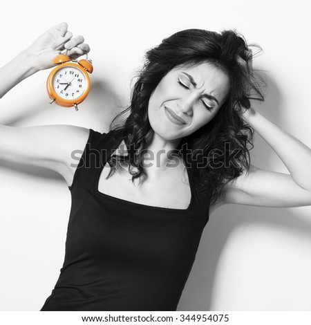 Portrait of young pretty unhappy woman with clock - stock photo
