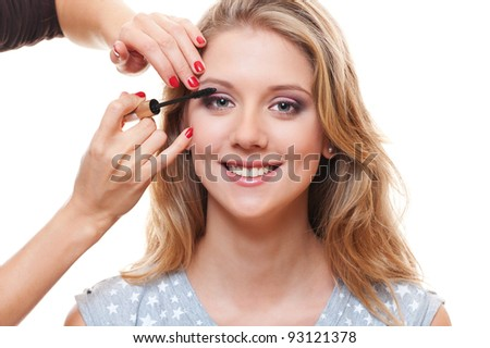 portrait of young pretty woman applying mascara over white background