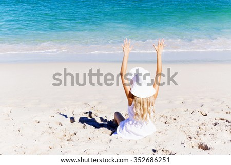 Portrait of young pretty woman cheering and relaxing on sandy beach