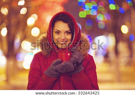 Portrait of young pretty woman drinking tea outdoor in wintertime over Christmas lights - stock photo