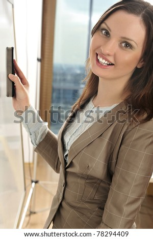 Portrait of young pretty woman erasing her presentation on white board - stock photo