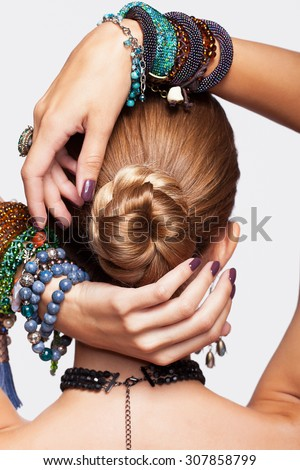 Portrait of young pretty woman from back side with hands on hair knot on gray background - stock photo