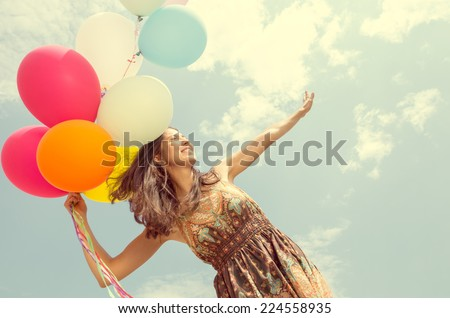 Portrait of young pretty woman holding balloons - Attractive model posing in front of camera outdoors - Vintage look - stock photo