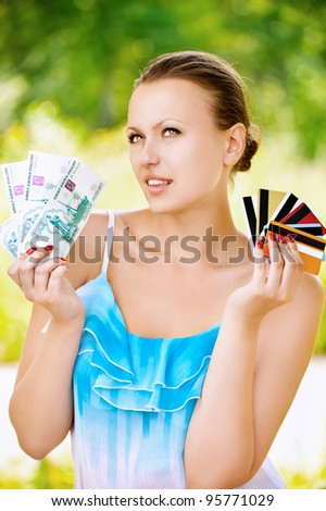 Portrait of young pretty woman holding credit cards and cash at summer green park - stock photo