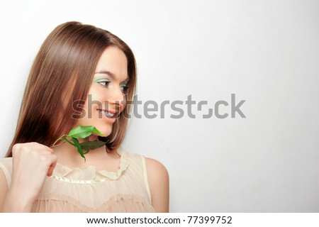 Portrait of young pretty woman holding green leaves in her hand standing near the wall with copyspace - stock photo
