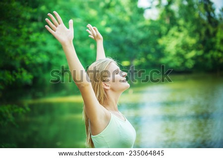 Portrait of young pretty woman holding hands up against lake at summer green park. - stock photo