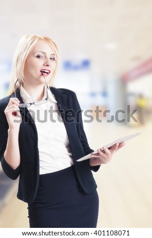 Portrait of young pretty woman holding tablet computer and glasses smiling  - stock photo