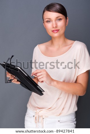 Portrait of young pretty woman holding tablet computer and glasses smiling on grey background. - stock photo