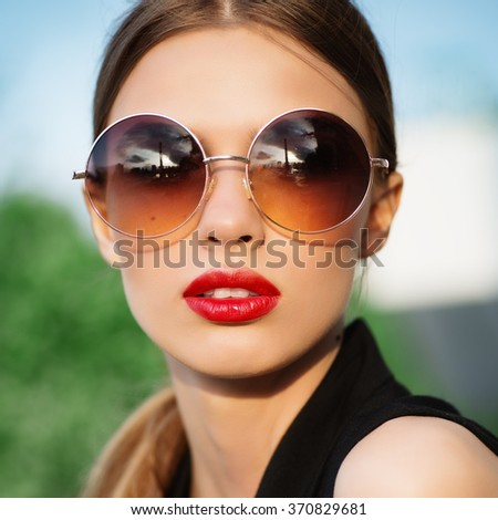 Portrait of young pretty woman in summer sunny day on street