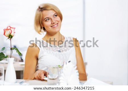 Portrait of young pretty woman sitting at cafe