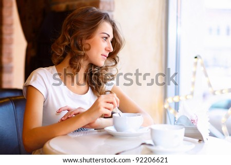 Portrait of young pretty woman sitting in restaurant - stock photo