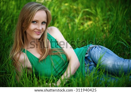 Portrait of young pretty woman sitting on green grass at summer green park