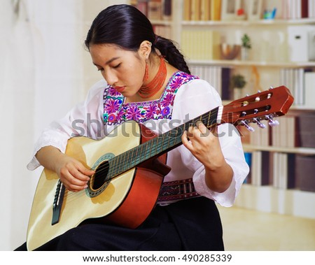 Portrait of young pretty woman wearing beautiful traditional andean clothing, sitting down with acoustic guitar playing, bookshelves background