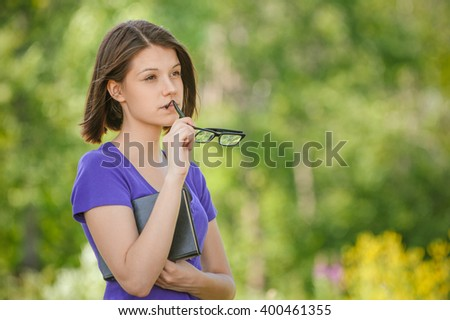 Portrait of young pretty woman wearing glasses holding book at summer green park - stock photo