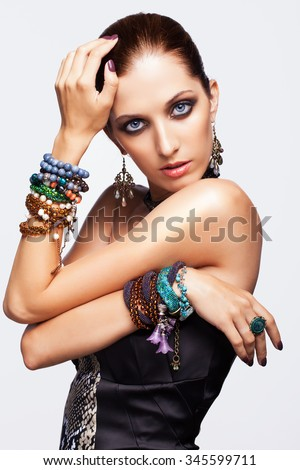 Portrait of young pretty woman with bijouterie on gray background