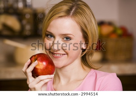 Portrait of young pretty woman with red apple in hand - stock photo