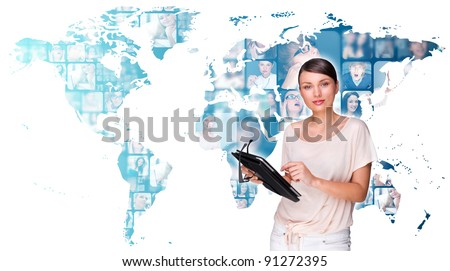 Portrait of young pretty woman working on modern tablet computer while standing against big virtual map with photo of her friends or colleagues - stock photo