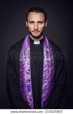 Portrait of young priest. Studio portrait on black background   - stock photo