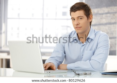 Portrait of young professional in office typing on laptop computer, looking at camera, smiling.?