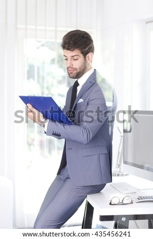 Portrait of young professional man holding clipboard in his hand and doing some paperwork while sitting at his workstation. - stock photo