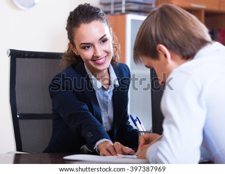 portrait of young professional teaching new employee in practice at company - stock photo