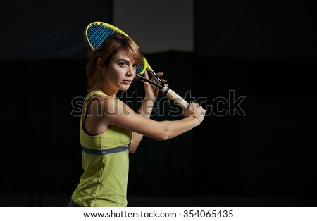 Portrait of young professional tennis player holding racket ready to serve. Pretty sportswoman playing tennis indoors in the gym. - stock photo
