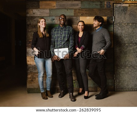 Portrait of young professionals laughing while standing together in office. Multi ethnic business team looking happy together. - stock photo