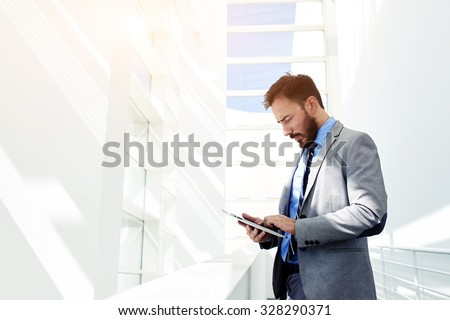 Portrait of young prosperous business man dressed in suit work on digital tablet during break, skilled male entrepreneur dressed in corporate clothes using touch pad while standing in modern office  - stock photo