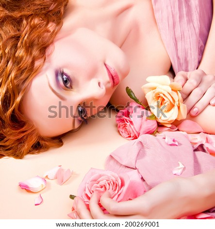 Portrait of young rad haired beautiful woman with stylish bright make-up and  with roses in her long  hair, lying on rose petals background.  - stock photo