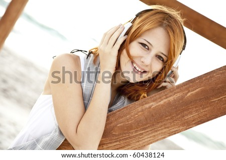 Portrait of young red-haired girl in headphone near wood at beach.