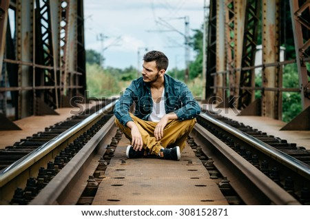 Portrait of young refugee man sitting on the railroad bridge. Vintage Instagram style effect, soft and selective focus, shallow DOF, strong clarity, grain texture visible on maximum size - stock photo