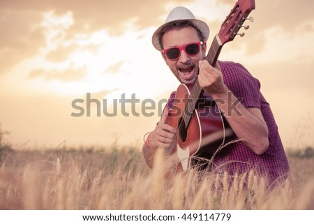Portrait of young retro styled man playing acoustic guitar and singing in wheat field. Sun and clouds in the background. Music, art and lifestyle concepts.   - stock photo
