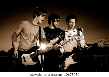 Portrait of young rock band performing - monochrome - stock photo