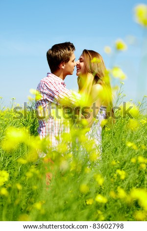Portrait of young romantic couple embracing one another in flower field - stock photo
