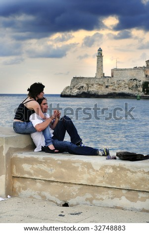 Portrait of young romantic couple relaxing on the havana malecon.